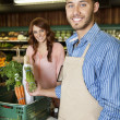 Portrait of a happy young sales clerk holding vegetables with woman in background — Stock Photo