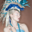 Beautiful young womwearing feather headgear with eyes closed — Stock Photo #21898991
