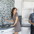 Royalty-Free Stock Photo: Young couple standing in model home kitchen while looking at each other