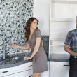 Young couple standing in model home kitchen while looking at each other — Stock Photo