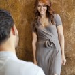 Stock Photo: Young woman looking at man while standing against wall