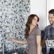 Beautiful young couple standing model home kitchen with color samples — Stock Photo