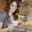Portrait of a happy young woman with tile samples in model home — Stock Photo #21899335