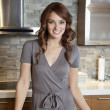 Portrait of beautiful young female with tile samples on kitchen counter - ストック写真
