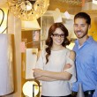 Portrait of a happy couple standing together in lights store — Stock Photo
