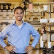Portrait of a handsome man standing with hands on hips in lights store — Stock Photo