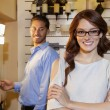 Portrait of a happy woman wearing glasses with arms crossed while man looking in background — Stock Photo #21899467