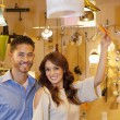 Portrait of young couple with price tag in lights store — Stock Photo