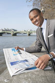 Portrait of African American businessman reading newspaper — Stock Photo
