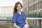 Portrait of a beautiful young female doctor having a coffee break — Stock Photo