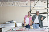 Portrait of happy team of architects with building plans at construction site — Stock Photo