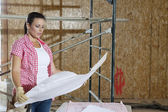 Young female contractor looking at building plans with scaffold in background — Stok fotoğraf
