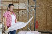 Contratista hembra joven mirando planos con andamios en fondo — Foto de Stock