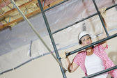 Young female construction worker climbing on scaffold — Foto Stock
