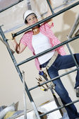 Vorderansicht der arbeitnehmerin klettern am gerüst — Stockfoto