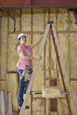 Female contractor climbing up the ladder at construction site — Stock Photo