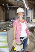 Portrait of a happy young woman architect wearing hardhat at construction site — Stock Photo