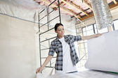 Beautiful mid adult contractor looking at building plans at construction site — Stock Photo