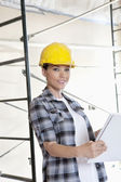 Portrait of beautiful mid adult architect wearing hardhat with blueprints — Stock Photo