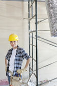 Portrait of mid adult woman standing with hands on hips at construction site — Stock Photo