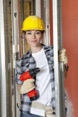 Portrait of beautiful mid adult contractor with drill — Stock Photo