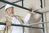 Portrait of mature man climbing scaffold — Stock Photo