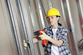 Mid adult worker drilling at construction site — Stock Photo
