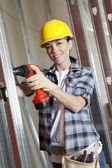 Portrait of a happy mid adult woman worker drilling at construction site — Stock Photo
