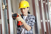 Mid adult female contractor drilling at construction site — Stock Photo