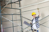 Beautiful female architect looking away while standing under scaffold — Stock Photo