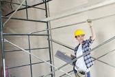 Hermosa mujer arquitecto apartar la mirada mientras está parado debajo de andamio — Foto de Stock