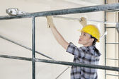 Back view of female contractor placing iron rod on scaffold — Foto Stock