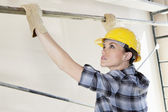 Woman worker placing rod on scaffold at construction site — Stock Photo