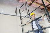 Female contractor climbing scaffold while looking away at construction site — Stockfoto