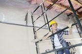 Contratista mujer andamio que sube mientras que apartar la mirada en el sitio de construcción — Foto de Stock