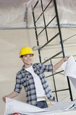 Happy mid adult worker holding building plans while looking away — Stock Photo