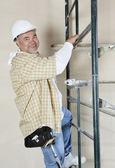 Porträt eines glücklichen arbeitnehmers gerüst klettern — Stockfoto