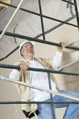 Front view of mature man climbing scaffold — Стоковое фото