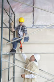 Male worker giving drill to woman on scaffold at construction site — Stok fotoğraf