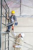Travailleur masculin donnant perceuse à femme sur échafaudage sur le chantier — Photo
