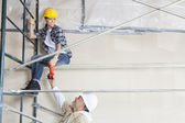 Male architect giving drill to female worker on scaffold at construction site — Stock fotografie