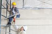 Arquitecto hombre dando taladro a trabajadora en andamio en construcción — Foto de Stock