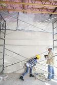 Trabajadores masculinos y femeninos de pie bajo el andamio en el sitio de construcción — Foto de Stock