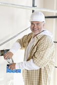 Portrait of a cheerful mature man holding construction equipment — Stock Photo