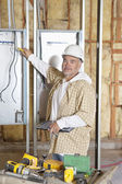 Portrait of a mature male construction worker checking electric meters at construction site — Stock Photo