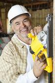 Feliz construcción hombre maduro trabajador corte de madera con una sierra circular — Foto de Stock