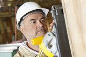 Piła poważny mężczyzna robotnik cięcia drewna z energii — Zdjęcie stockowe