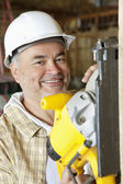 Portrait of a smiling male construction worker cutting wood with a circular saw — Stock Photo