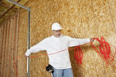 Mature male construction worker with an electrical wire — Stock Photo