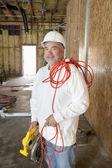 Portrait of a smiling male construction worker holding a power saw and a red electric wire — Stock Photo